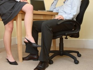 I'm Afraid My Husband is Not Being Faithful - Carla Anne Coroy - office romance woman showing off leg by propping on man's desk