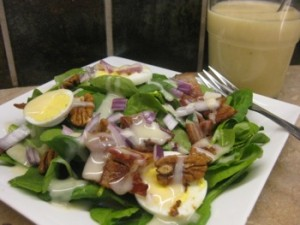 Spinach Salad with Lemon Bacon Dressing - Carla Anne Coroy - Spinach Salad with Lemon Bacon Dressing plated with dressing in a cup